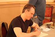 Photo of author Bill Kenower signing his book at the 2014 Willamette Writers meeting in Portland.