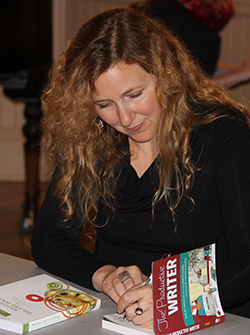 Photo of poet Sage Cohen signing a book at the Old Church.